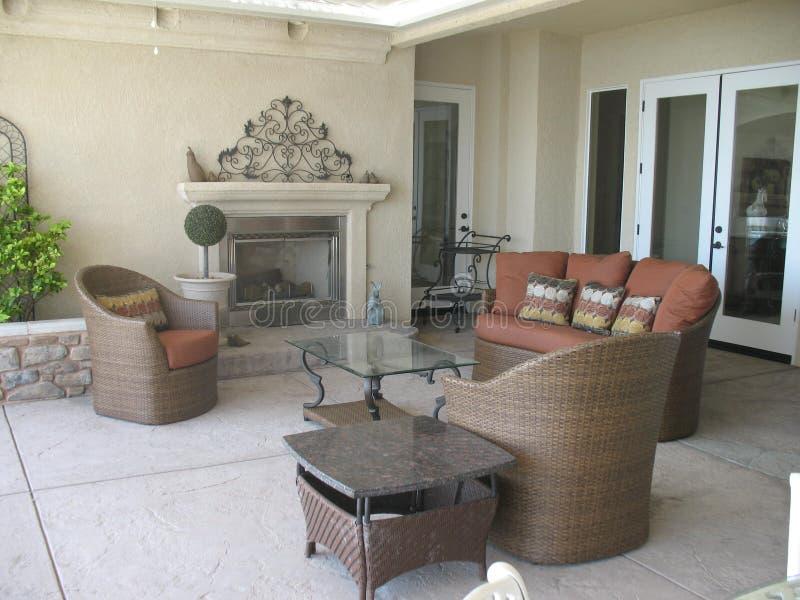 Patio im Freien mit Kamin-und Flechtweiden-Möbeln lizenzfreies stockfoto