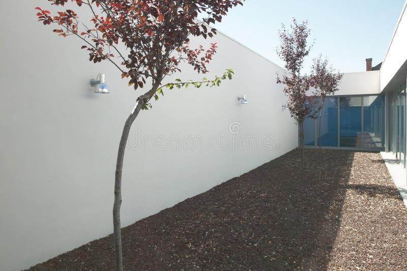 Patio moderne de maison avec des arbres et des pierres photos stock