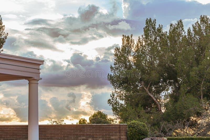 Patio murato del giardino con i sempreverdi e il cloudscape di trascuratezza dell'orizzonte del legno di bosso fotografia stock
