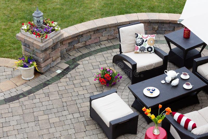 Patio pavimentado ladrillo con muebles del patio imagen de archivo