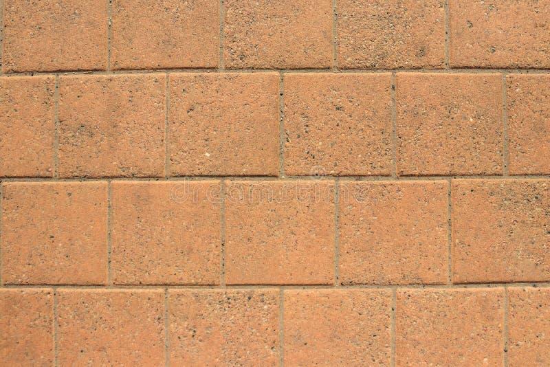 Patio paving orange tiles, stone background, wall of blocks royalty free stock photography