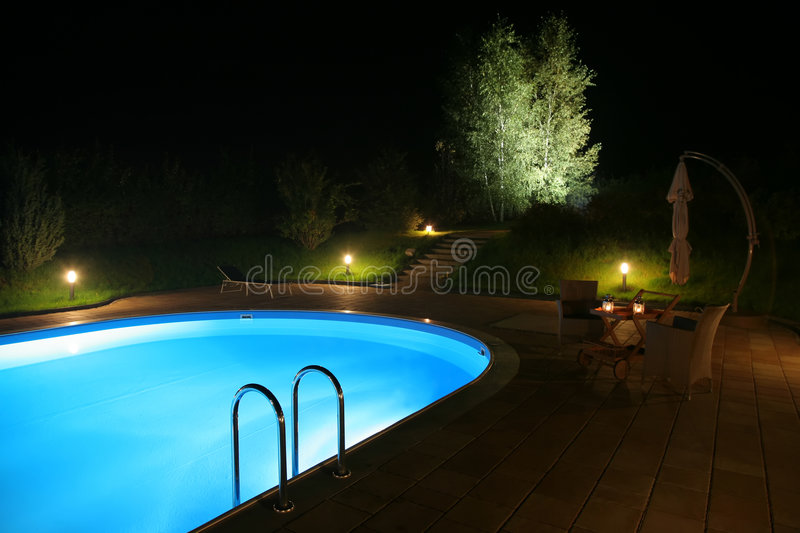 Patio and Pool by Night-2. Beautiful night view of a private backyard pool and patio with comfortable lounge furnature that make for a very romantic evening
