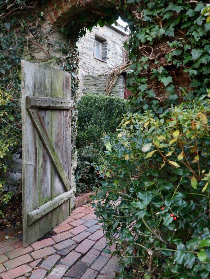 Patio rústico con la puerta y la trayectoria de madera del ladrillo foto de archivo