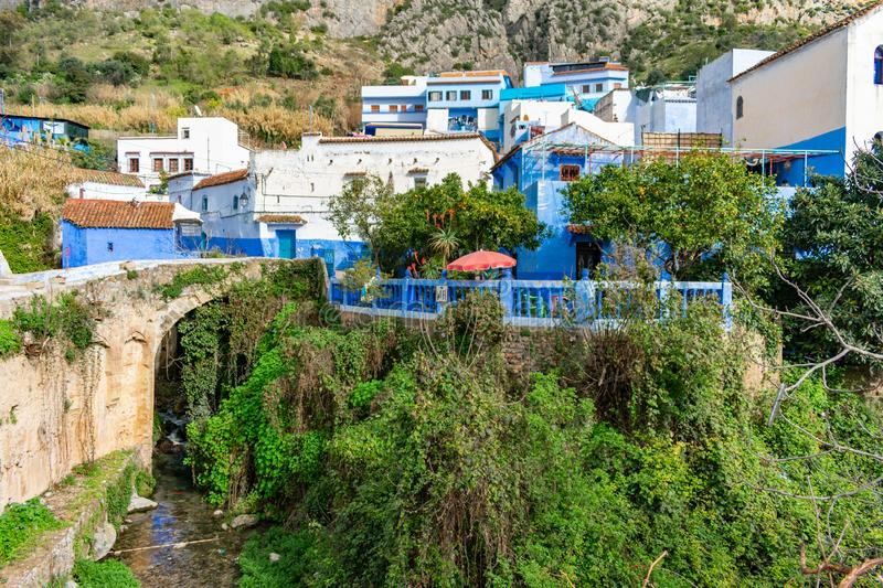Patio with Red Umbrella beside a Stream with Blue and White Colored Homes and Buildings in Chefchaouen Morocco. A patio lookout with a red umbrella beside a royalty free stock photography