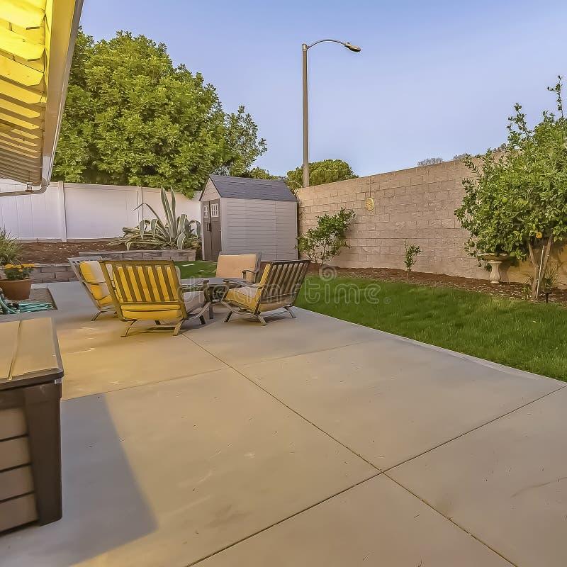 Patio spacieux à l'arrière-cour d'une maison avec une allocation des places et une salle à manger image stock