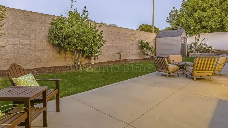 Patio spacieux de cadre de panorama à l'arrière-cour d'une maison avec une allocation des places et une salle à manger photographie stock