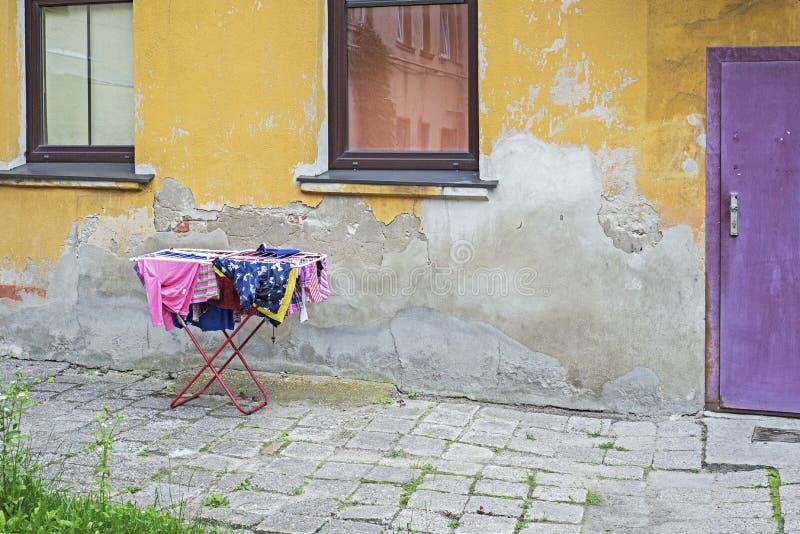Patio trasero de la casa resistida vieja del grunge Pared amarilla y puerta violeta foto de archivo