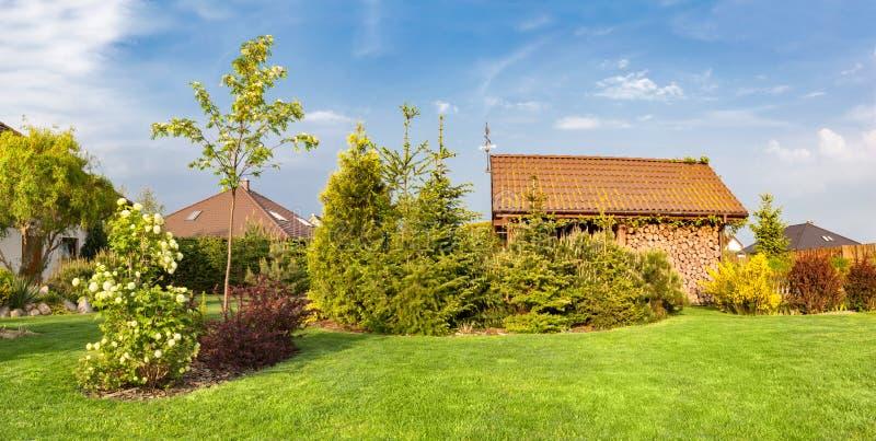 Patio trasero de una casa de la familia Jardín ajardinado con la hierba segada verde, refugio de madera imagen de archivo