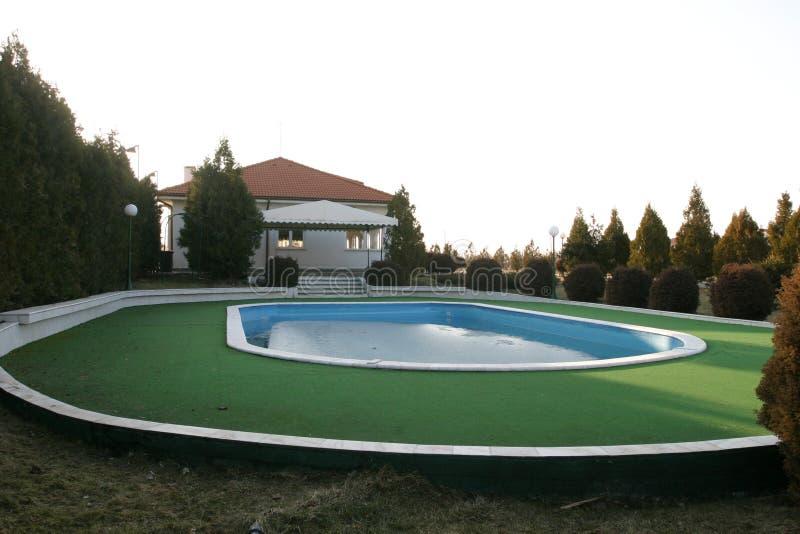 Patio trasero del chalet con la piscina grande fotografía de archivo