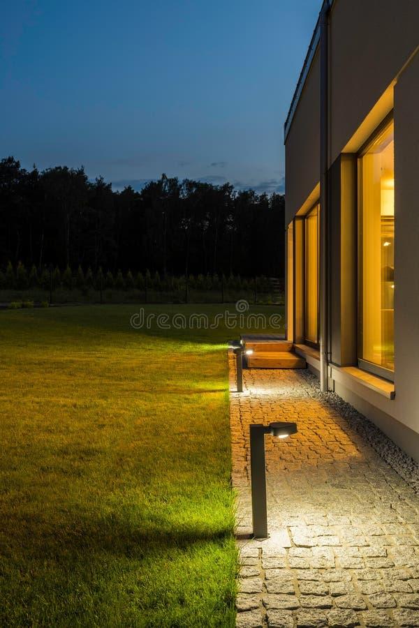 Patio trasero del chalet iluminado en la noche fotos de archivo libres de regalías