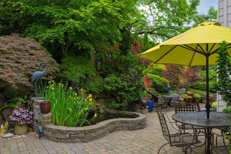 Patio trasero Hardscape de la casa con muebles del patio del jardín fotos de archivo libres de regalías
