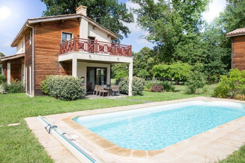 Patio trasero moderno con la piscina y el área entretenida imágenes de archivo libres de regalías