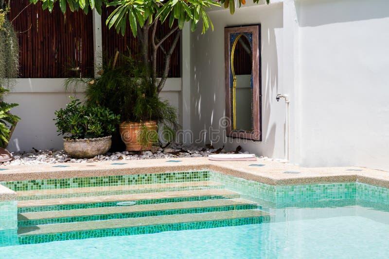 Patio trasero moderno de una piscina con agua clara imagen de archivo
