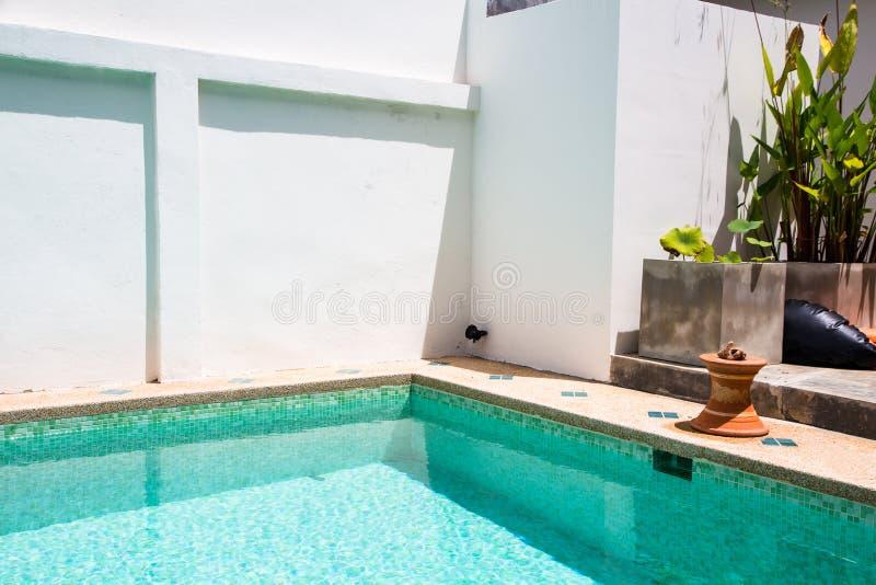 Patio trasero moderno de una piscina con agua clara foto de archivo libre de regalías