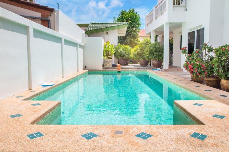 Patio trasero moderno de una piscina con la casa imágenes de archivo libres de regalías