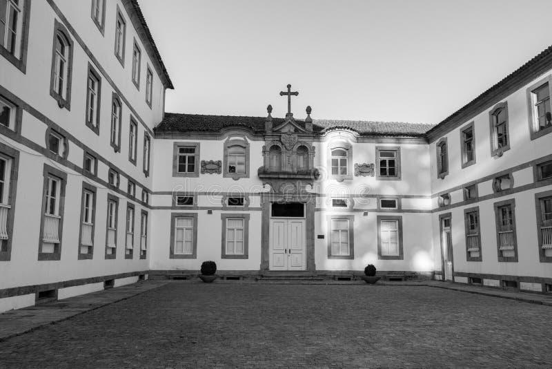 Patio trasero vac?o del monasterio antiguo en el monocromo de Europa Exterior del monasterio con la cruz en el tejado blanco y ne fotografía de archivo