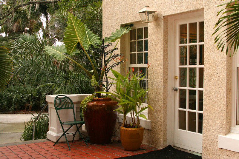 Patio in Tropics. With plants in pots on red tiled floor, French doors, Bird of Paradise, palms, and other tropical plants stock image