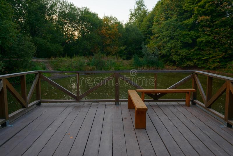 Patio z ogrodzeniem i ławką przegapia małego staw fotografia stock