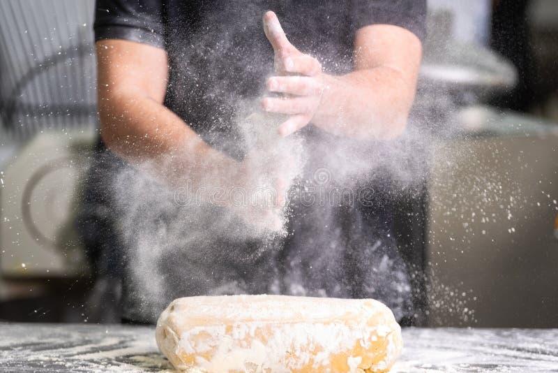 Patissier, der seine Hände mit Mehl bei der Herstellung des Teigs klatscht stockbilder