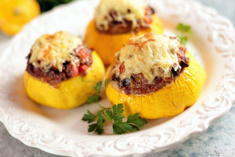 Patissons gialli organici farciti con carne, le cipolle, le carote, i funghi ed il peperone al forno nel forno con formaggio fotografia stock libera da diritti