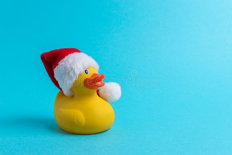 Pato de borracha com o chapéu de Santa no fundo azul Conceito do Natal m?nimo ou do ano novo imagem de stock royalty free