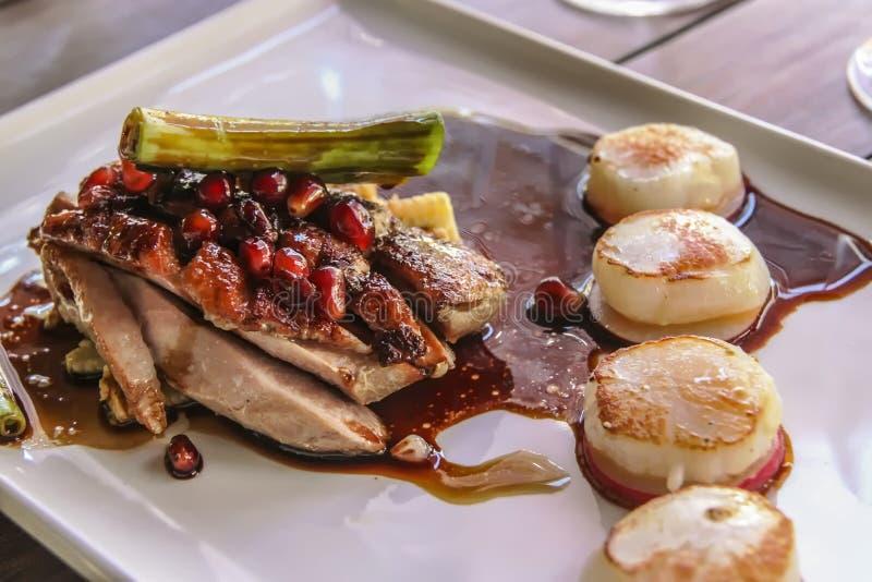 Pato de carne asada con las conchas de peregrino chamuscadas en un restaurante del lagar fotos de archivo libres de regalías