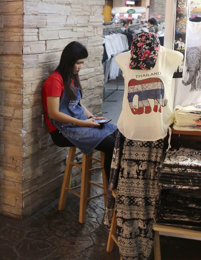 PATONG PHUKET, THAILAND - JULI 24, 2019: Den oidentifierade asiatiska unga kvinnan använder smartphonen som sitter på en stol på  fotografering för bildbyråer