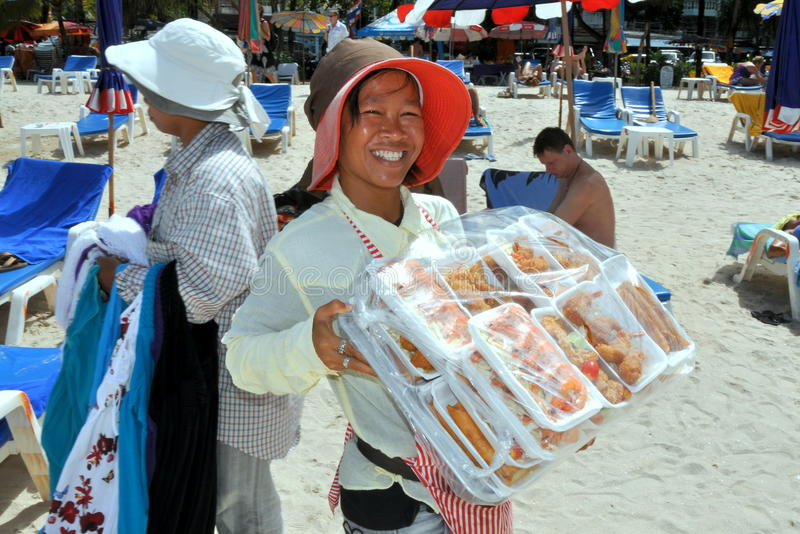 Patong, Thailand: Woman Selling Food on Beach. Smiling woman strolls along Patong Beach selling food in styrofoam boxes covered with plastic wrap to beachgoers royalty free stock image
