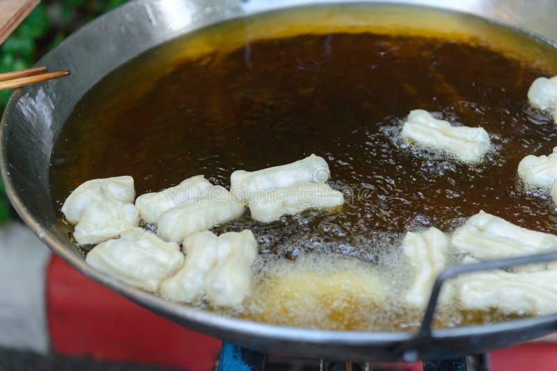Patongko - friggere il bastone fritto nel grasso bollente della pasta fotografia stock