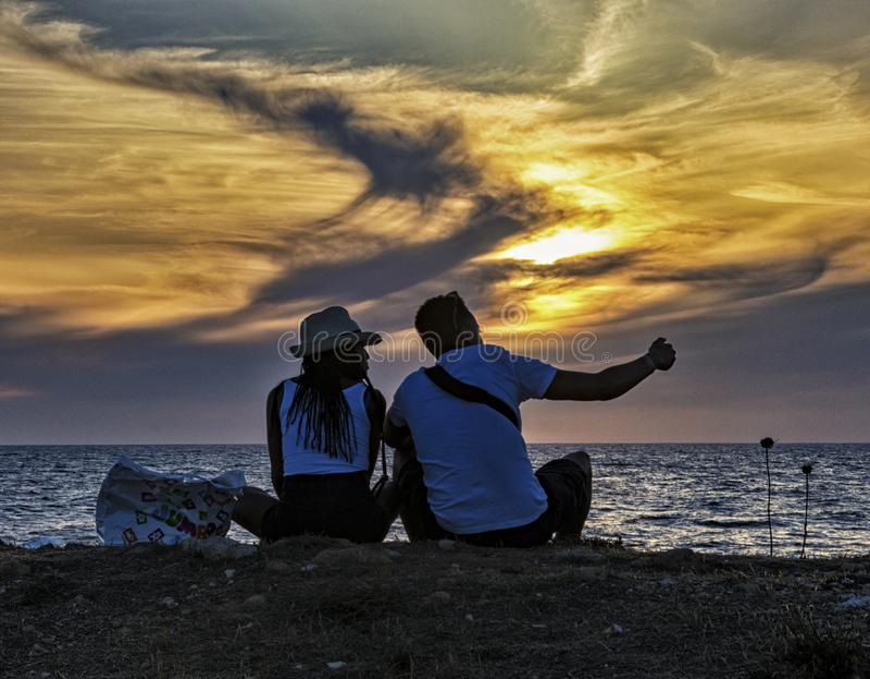 Patos, Chipre - 19 de mayo de 2016 - Una pareja joven se sienta en la playa y disfruta de la puesta de sol fotografía de archivo