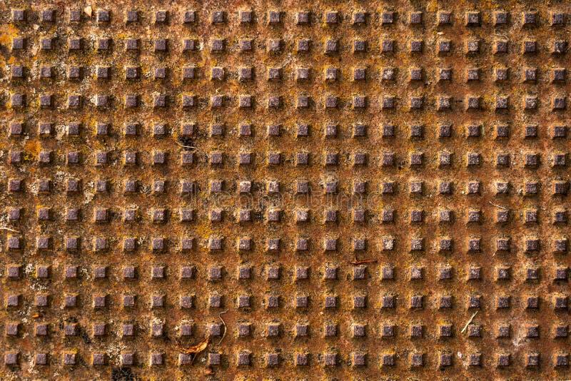 Patrón de agujeros con un diseño metálico cuadrado en la parte superior de la vista de cierre marrón fotos de archivo