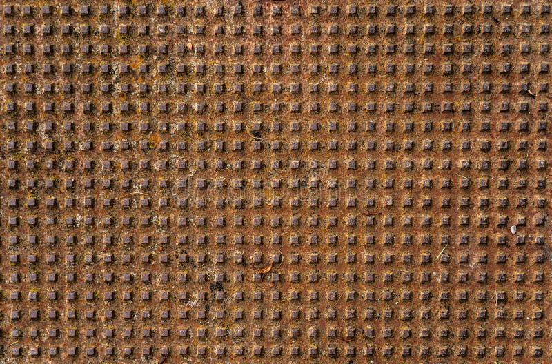 Patrón de agujeros con un diseño metálico cuadrado en marrón fotografía de archivo
