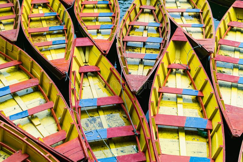 Patrón de botes de madera rojos y amarillos amarrados uno al lado del otro en Pokhara, Nepal imagen de archivo libre de regalías