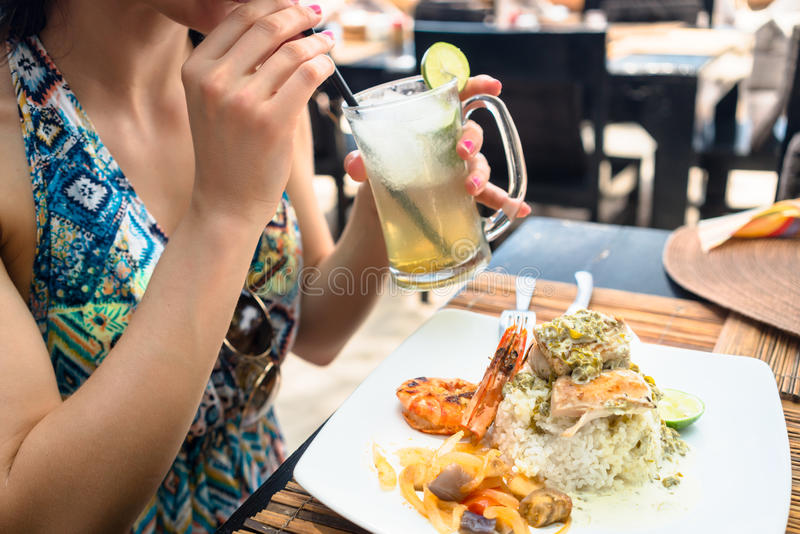 Patrón de la mujer que come los mariscos y que bebe el cóctel en restaurante fotografía de archivo