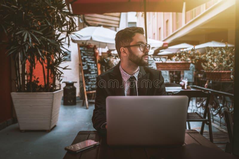 Patrón de vacilación del hombre con el ordenador portátil que espera en restaurante de la calle imagen de archivo