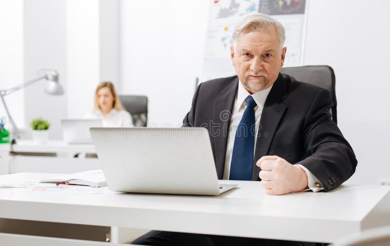 Patrón envejecido impaciente que expresa furia en la oficina imágenes de archivo libres de regalías