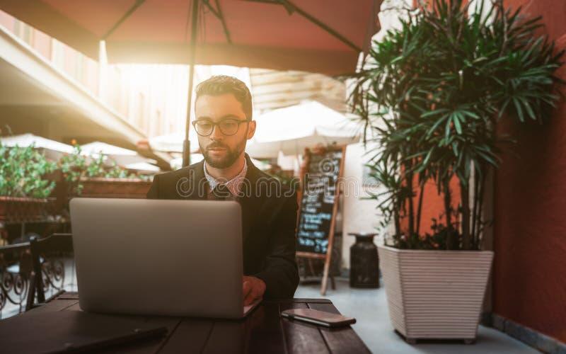 Patrón hermoso joven del hombre en el restaurante al aire libre con el ordenador portátil fotografía de archivo