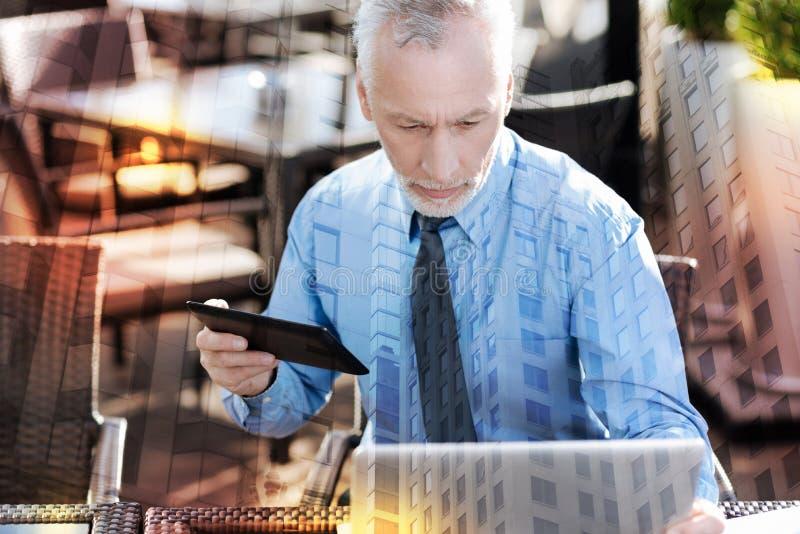 Patrón maduro serio que mira la pantalla mientras que trabaja fotografía de archivo