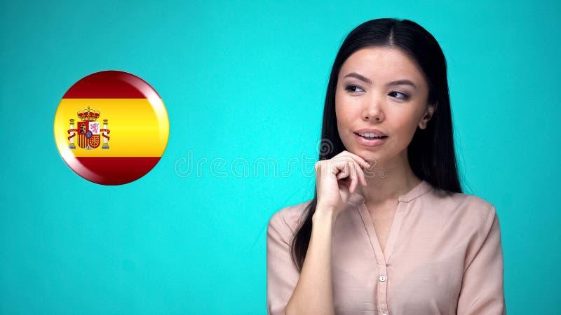 Patriota femenino hermoso que mira cuidadosamente la muestra española de la bandera, elección foto de archivo libre de regalías