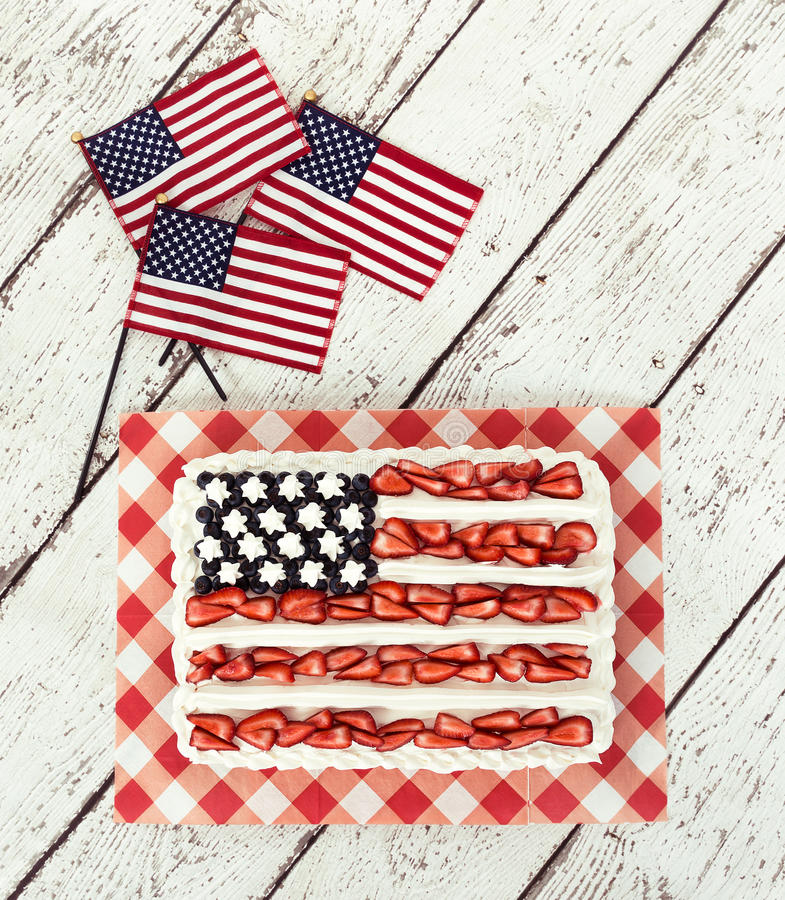 Patriotic American flag cake with mini flags. Patriotic American flag cake and decorative mini flags on vintage wooden background royalty free stock photo