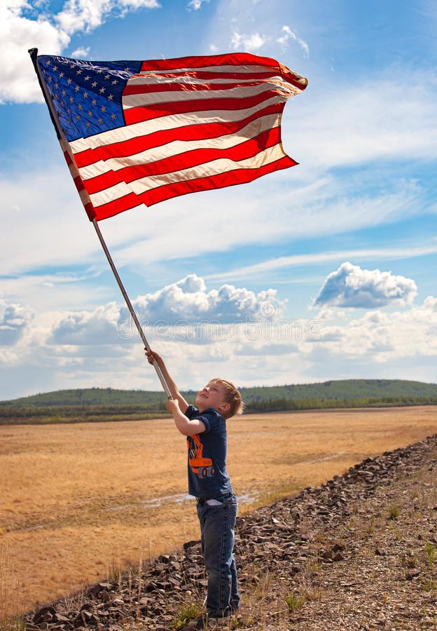 Patriotic boy with American flag royalty free stock photography