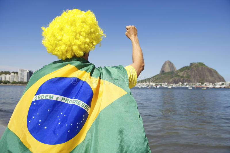 Patriotic Brazil Fan Standing Wrapped in Brazilian Flag Rio. Patriotic Brazilian fan standing wrapped in flag raising fist in front of Sugarloaf Mountain royalty free stock images