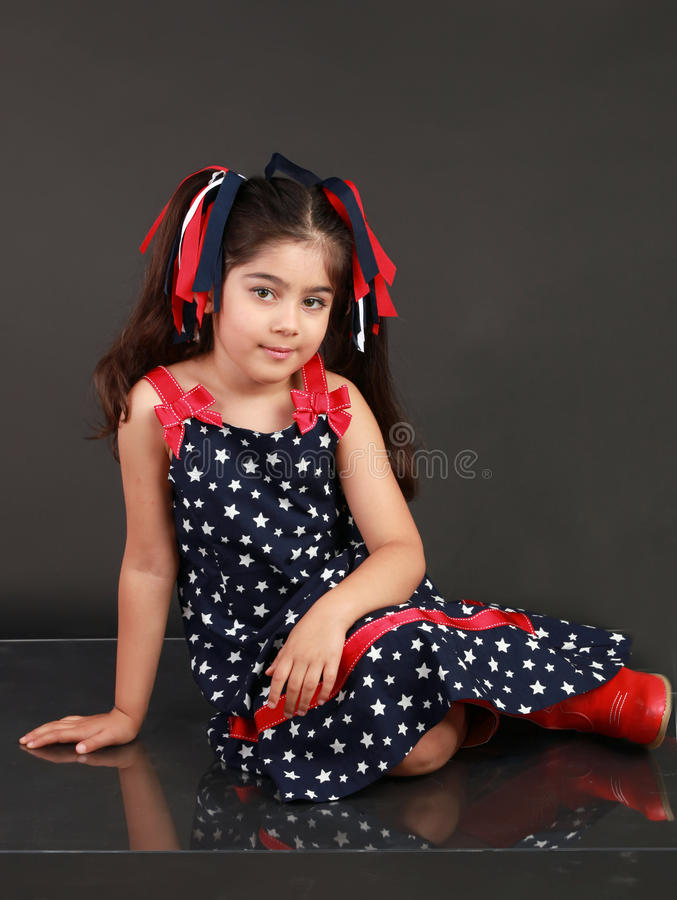Patriotic Child. A young girl dress in US flag pattern and shows her patriotism to the USA on 4th of July royalty free stock photography