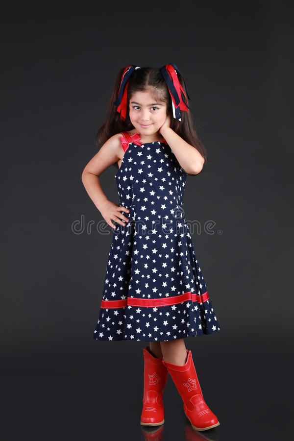 Patriotic Child. A young girl dress in US flag pattern and shows her patriotism to the USA on 4th of July royalty free stock photos