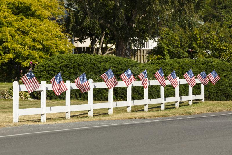 Patriotic display of American flags waving on white picket fence next to a road. Typical small town USA 4th of July decorations. royalty free stock photography