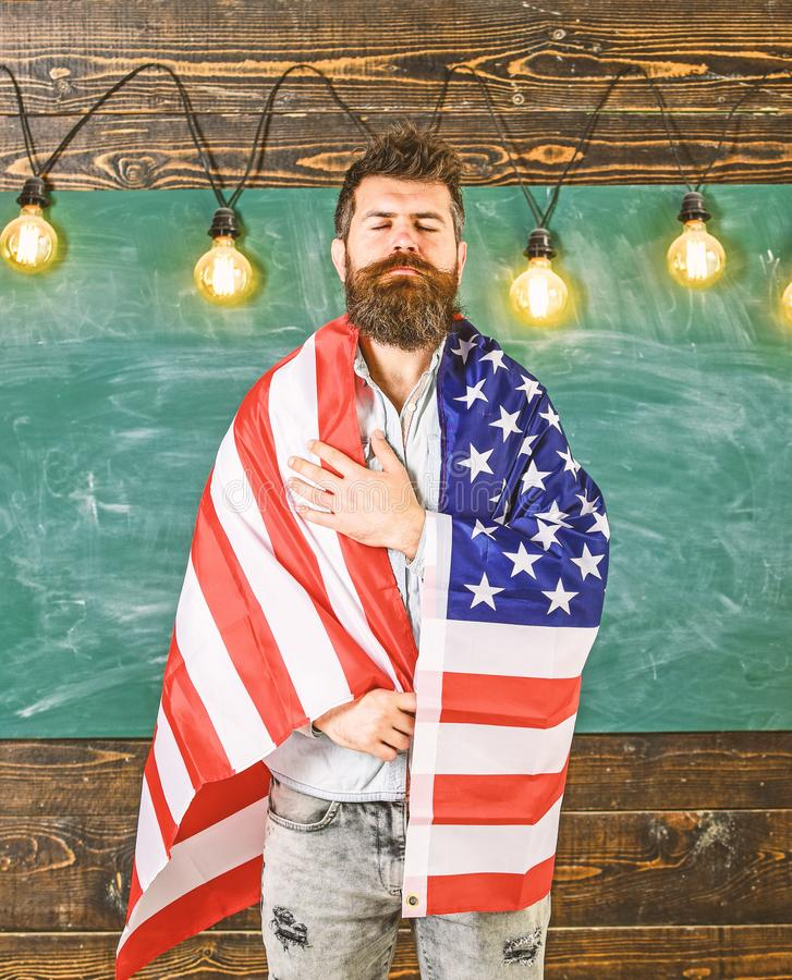 Patriotic education concept. American teacher covered with american flag. Teacher teaches to love homeland, USA. Man. With beard and mustache on serious face royalty free stock photography