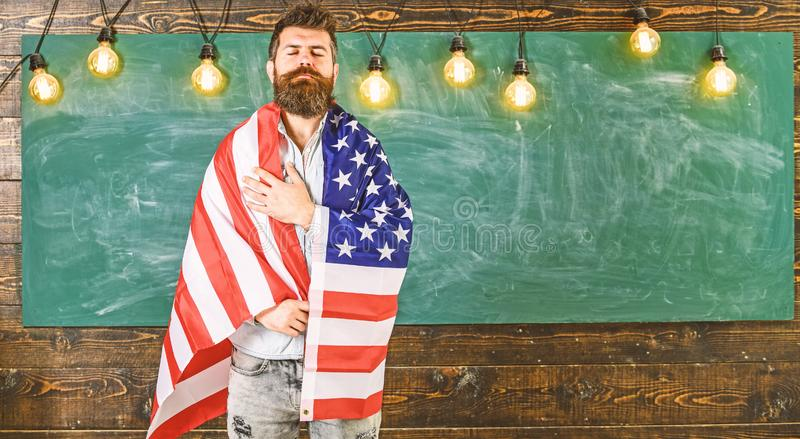Patriotic education concept. Teacher teaches to love homeland, USA. Man with beard and mustache on serious face with. Flag of USA, chalkboard on background stock image