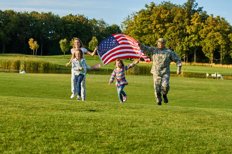 Patriotic family running with huge american flag. stock photos