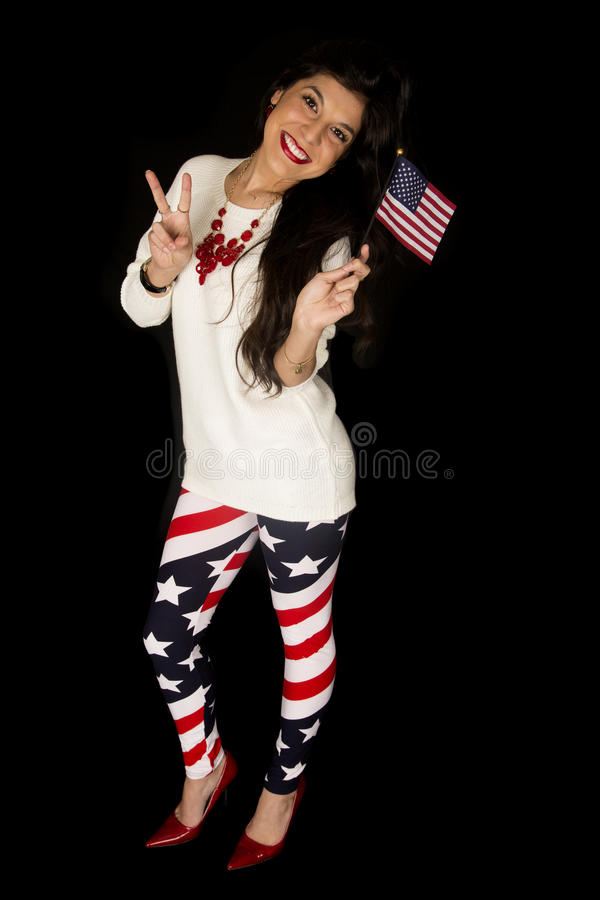 Patriotic female holding an American flag showing the peace sign. Patriotic female holding flag showing peace sign royalty free stock photography