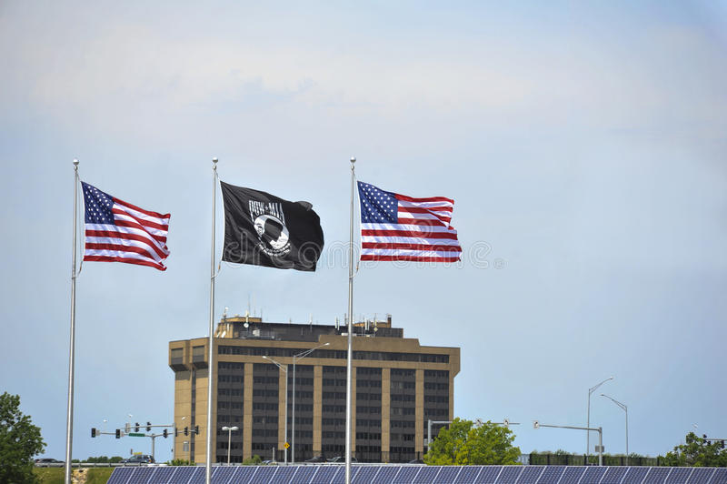 Patriotic Flags. Three flags — two United States and one POW/MIA — fly over a city and stadium stock image